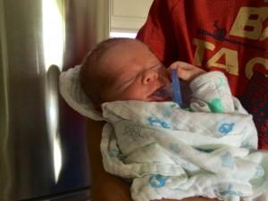newborn holding his paci.
