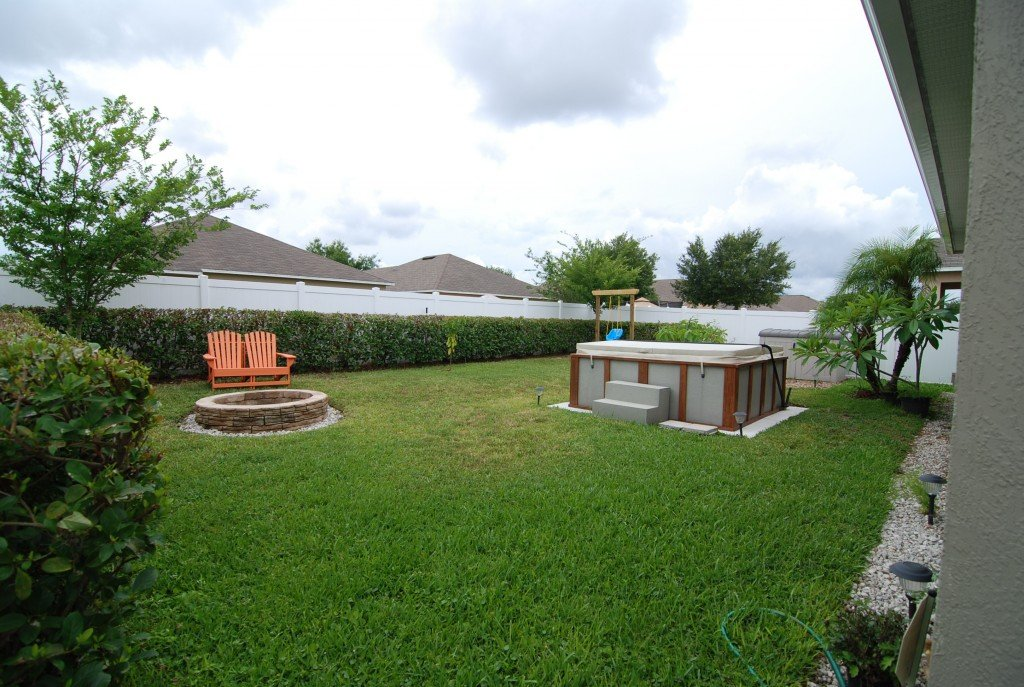 back yard with hot tub and fire place